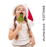 Little girl busy licking a christmas tree shaped candy - isolated - stock photo
