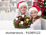Kids smiling with self decorated advent wreath at christmas time - stock photo
