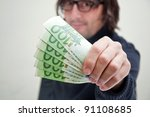 Casual adult man is paying in euros, corruption and bribe concept. - stock photo