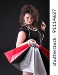 lovely woman with shopping bags over black background - stock photo