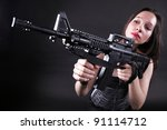 Sexy women - Girl holding an Assault Rifle, black background - stock photo