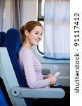 Young woman traveling by train, holding her train ticket , smiling - stock photo
