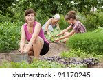 Three women working in her vegetable garden - stock photo