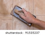 Man's hand with grout trowel while working on ceramic tile - stock photo