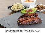 Daeji Galbi - Grilled Korean pork spare ribs served with ssamjang (mixed paste), kimchi (fermented cabbage), beoseot jorim (stir-fry mushrooms) and kongnamul muchim (seasoned beansprout). - stock photo