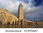 Front of ornate Hassan II Mosque showing rows of tiled archways and minaret. - stock photo