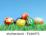 Painted easter egg in grass over blue sky - stock photo