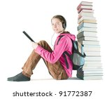 Small photo of Teen girl reads ebook sitting near the stack of printed books