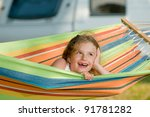 Summer vacation in camping - Cute girl in the colorful hammock - stock photo