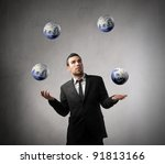 Young businessman juggling with some earth planets - stock photo
