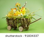 Wicker cart with Easter chick and eggs over light green background - stock photo