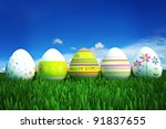 Happy Easter, colored eggs in a grass field with a clear blue sky. Room for text and copy space - stock photo