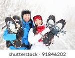 Winter couple happy outdoor hiking in snow on snowshoes. Healthy lifestyle photo of young smiling active mixed race couple snowshoeing outdoors. Asian woman, caucasian man. - stock photo