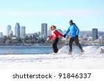 Winter fun couple on snowshoes running with montreal cityscape skyline and river st. Lawrence in background. Healthy lifestyle photo from Montreal, Quebec, Canada. - stock photo
