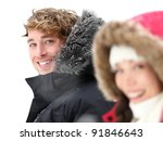 Outdoor couple smiling in winter snow. Focus on Caucasian male model in warm winter clothing. Asian woman, Caucasian male in their 20s. - stock photo