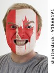High key portrait of an angry man whose face is painted in colors of canada flag - stock photo