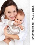 Happy mother and beautiful baby girl sitting on the floor - top view - stock photo