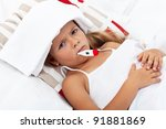 Sick little girl with thermometer and cold pack laying in bed - stock photo