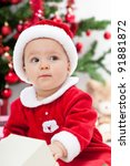 Beautiful baby girl in front of the christmas tree wearing santa clothes - closeup - stock photo