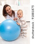Baby girl stands by a large ball with a little help from her mother - stock photo