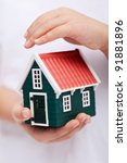 Protecting your home - child hands shielding house - stock photo