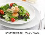 Closeup of a plate of scallops, cherry tomatoes and spring mix salad with Saffron dressing. - stock photo