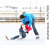 Ice skating couple having winter fun on ice skates in Old Port, Montreal, Quebec, Canada. - stock photo