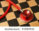 A medical strategy concept containing a stethoscope and chess board. - stock photo
