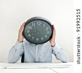 Time management. Businessman with a clock instead of his head, looking desperately down as the time passes by. - stock photo