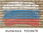 Chalky russian flag painted with color chalk on grunge old brick wall - stock photo