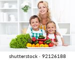 Woman and kids wearing aprons preparing vegetables in the kitchen - stock photo