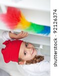 Little girl doing chores - dusting and cleaning with feather duster - stock photo