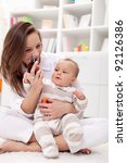 Happy young mother playing with her beautiful baby girl - stock photo