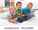 Happy kids with laptop computer laying on the floor - stock photo