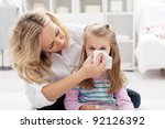 Woman at home blowing the nose of her little girl - stock photo