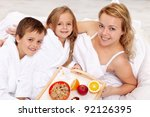 Breakfast in bed for our mom - kids pampering their mother - stock photo