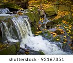 A small waterfall and stream surrounded by fallen leaves in the Pocono Mountains of Pennsylvania. - stock photo