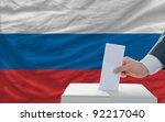 man putting ballot in a box during elections in russia in front of flag - stock photo