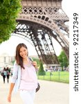 Paris woman by Eiffel Tower. Smiling young happy woman walking in front of the Eiffel Tower, Paris, France. Candid image. - stock photo