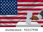 man putting ballot in a box during elections in america in front of flag - stock photo
