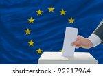 man putting ballot in a box...
