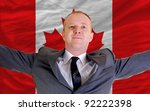 joyful investor spreading arms after good business investment in canada, in front of flag - stock photo