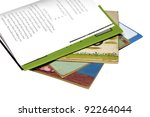 Old story books with a new one on top opened to a story page. - stock photo