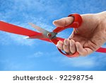 Businessman cutting a red ribbon with a pair of scissors - stock photo