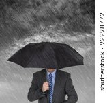Businessman with umbrella protecting himself from the storm concept for protection from recession or economic depression etc - stock photo