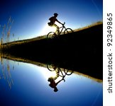 Mountain biking up a trail in the mountains silhouetted reflection in water - stock photo