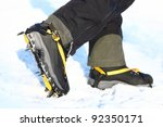 Crampons and shoes walking on ice and snow during outdoor winter trekking. Close up. - stock photo