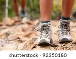 Hiking shoes close up outoors during hike - female shoes. Hikers in the background - stock photo