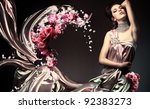 sensual woman in long light dress with flowers - stock photo