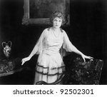 Small photo of Woman in a tulle dress standing next to an armchair